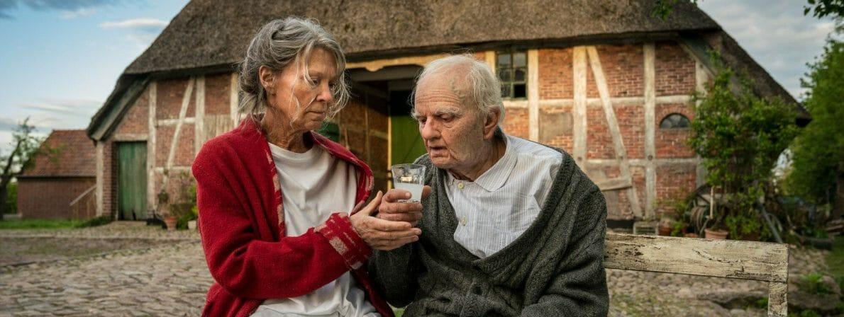 Vera Eckhoff (Iris Berben) erfüllt ihrem Stiefvater Karl (Milan Peschel) auf der weißen Bank vor dem Haus einen langgehegten Wunsch. (Foto: ZDF/Georges Pauly)