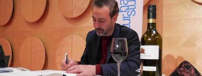Stilvoll mit Rotwein: Claudio Caiolo signiert zum ersten Mal einen eigenen Roman nach der Premierenlesung in Stuttgart (Foto: Wolfgang Tischer)