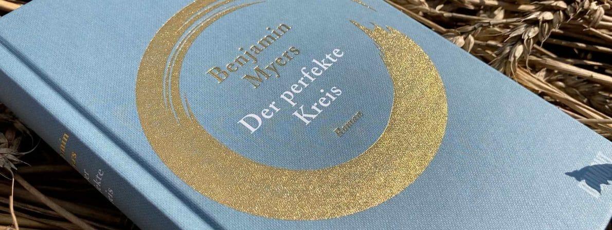Ein Buch im Kornfeld: Goldgelben ist auf dem Cover ein Ensō dargestellt.