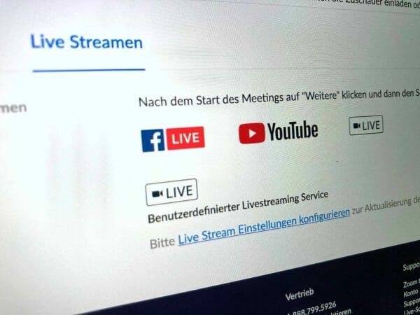 Nicht ganz so einfach und versteckt, aber man kann Zoom-Meetings bei YouTube und Facebook streamen