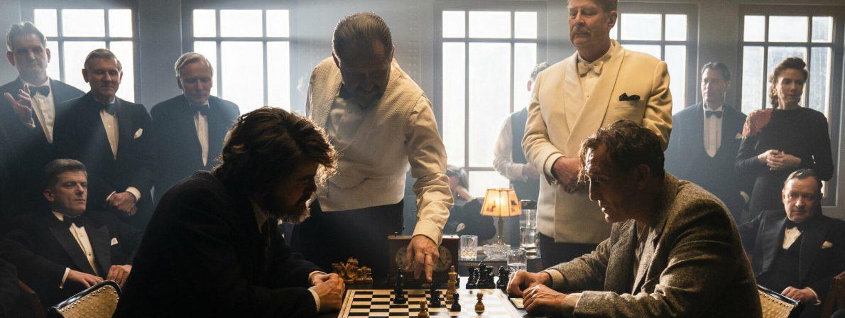McConnor (Rolf Lassgård, 2. v. r.) bittet Bartok(Oliver Masucci, r.) die Partie mit Czentovic (Albrecht Schuch, l.) weiterzuspielen (Foto: Studiocanal)