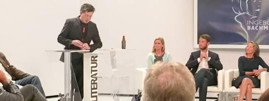 Franzobel bei seiner Klagenfurter Rede zur Literatur. Links daneben die Jurorin Meike Feßmann, Juror Michael Wiederstein und Jurorin Hildegard Keller.
